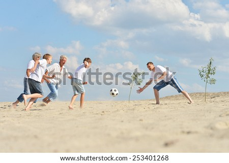 Big Family playing football on a beach in summer day - stock photo