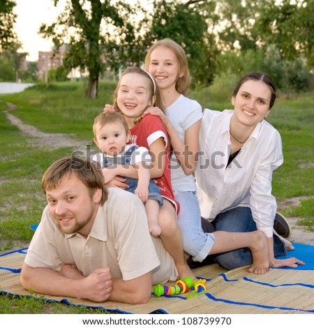 Big family - smiling father, mother and three daughters on the green grass in the park. Happy family concept - stock photo