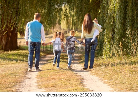 Big family walking in the park. Rear view. Family ties concept.