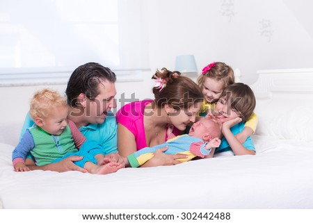 Big family with four kids relaxing in bed on a sunny morning. Parents with newborn baby, toddler boy, preschooler girl and teenager son in a white bedroom. Mother and father playing with children. - stock photo