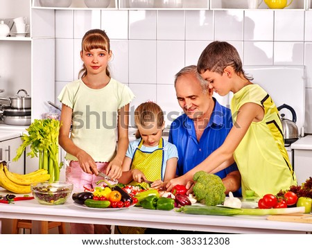 Big family with kids cooking at kitchen. Grandfather and children. - stock photo