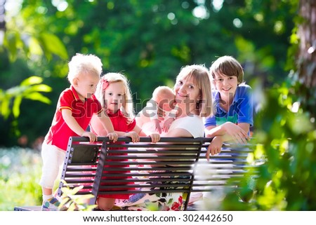 Big family with kids playing in a park. Woman and children relax on a bench in the garden. Grandmother and grandchildren play outdoors in summer. Mother with baby, toddler, preschooler and teenager. - stock photo