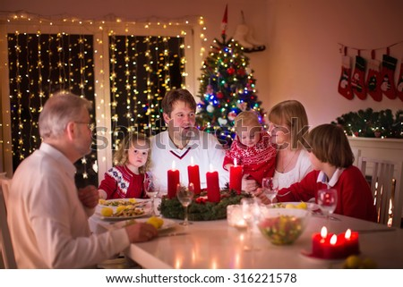 Big family with three children celebrating Christmas at home. Festive dinner at fireplace and Xmas tree. Parent and kids eating at fire place in decorated room. Child lighting advent wreath candle. - stock photo