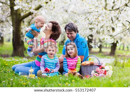 Big family with three little children eating lunch outdoors. Parents and kids with picnic basket in spring garden. Mother, father, preschooler girl, toddler boy and baby eat and drink in summer park