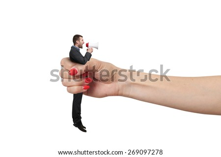 big female hand holding in fist small man and he screaming at megaphone. isolated on white background - stock photo
