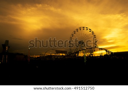 Big Ferris wheel swing at amusement park in silhouette sunset,