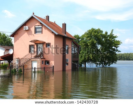 big flooded house with blue sky and white clouds in high water - stock photo