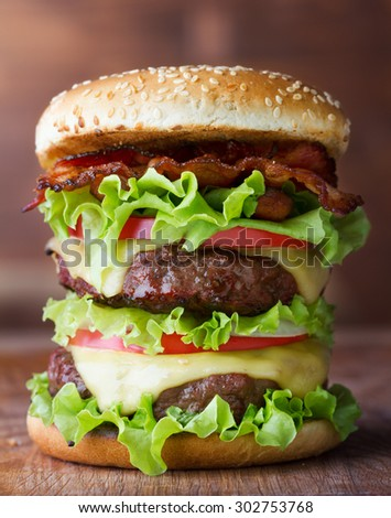 big fresh burger with cheese and bacon on wooden table