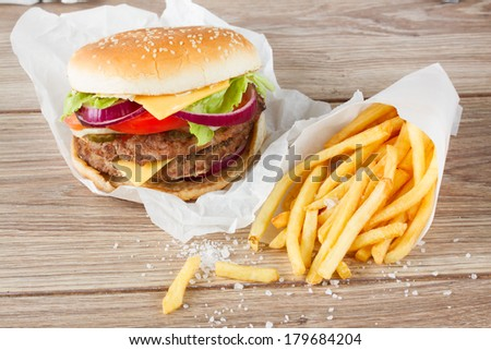 Big fresh  hamburger with french fries on wooden table