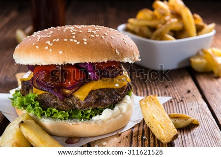 Big fresh made Burger on rustic wooden background (with French Fries) - stock photo