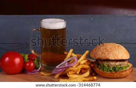 Big fresh tasty burger of green lettuce meat cutlet cheese tomato and white bread bun with sesame seeds near chips and glass of light beer on octoberfest holiday on grey background, horizontal picture - stock photo