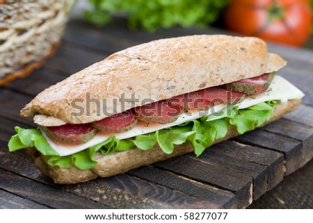 Big freshly made sandwich with lettuce , cheese and meat - stock photo