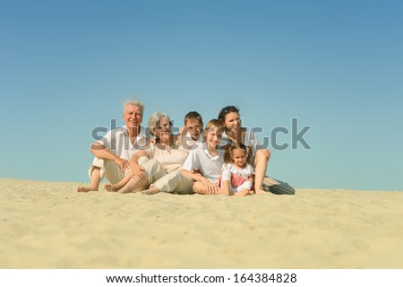 big friendly family relaxing on the sand together - stock photo