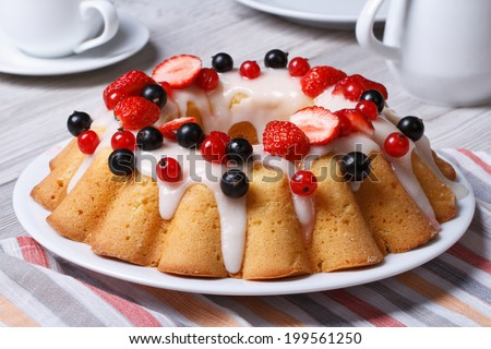 big fruit cake with icing, decorated with strawberries and currants close-up on the table. horizontal  - stock photo