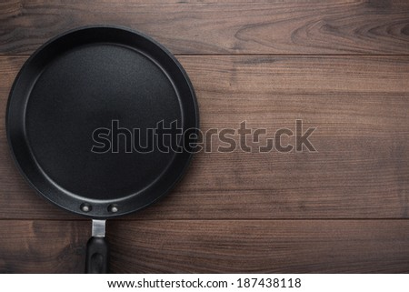 big frying pan on the table background - stock photo