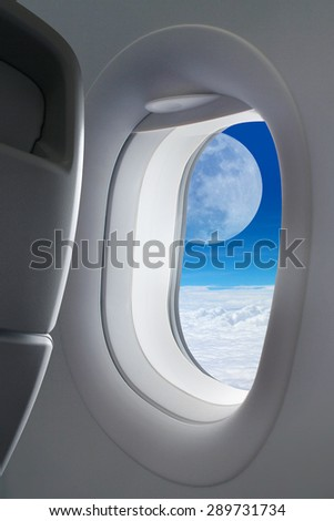 Big full moon view with white flat cloud on blue sky outside the window plane and black passenger seat