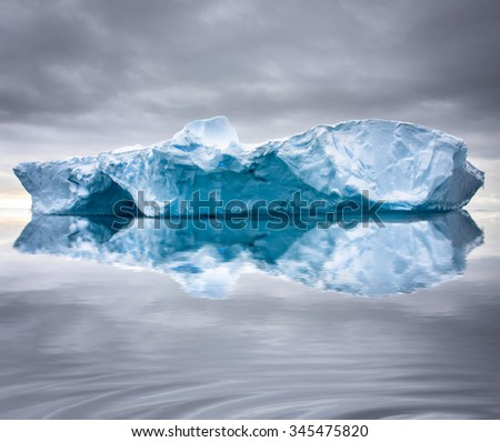Big glacier in the snow with reslection in water - stock photo