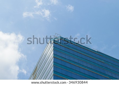 Big glass building with blue sky and white cloud
