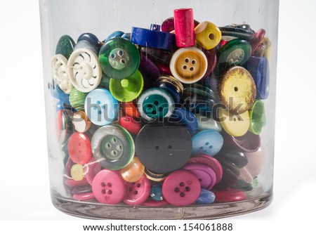 Big glass jar containing lots of colorful vintage buttons. - stock photo