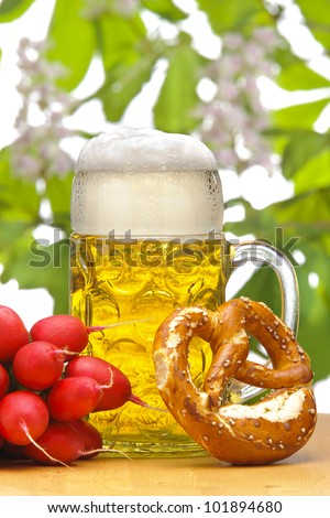 big glass of german bavarian beer at munich octoberfest with radish and pretzel - stock photo