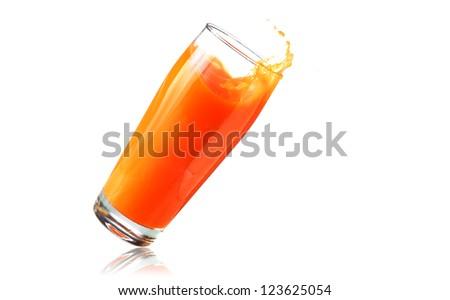 Big glass of orange juice falling over - stock photo