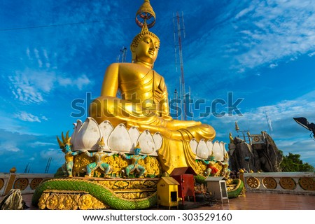 Big Golden Buddha statue against blue sky in Thailand temple - stock photo