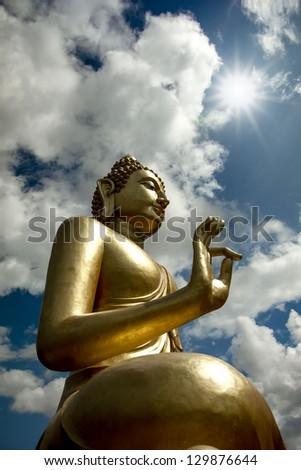 Big golden Buddha statue on the sky sunny day. - stock photo