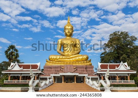 big golden buddha statue sitting in thai temple on blue sky background - stock photo