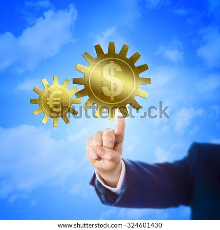 Big golden cogwheel carrying the Dollar symbol is interlocking with a small gear wheel embossed with the Euro sign. Hand of a trader touching the larger cog. Financial metaphor for currency exchange. - stock photo