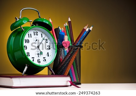 Big green alarm clock with notepad, black holder and pencils on dark yellow background