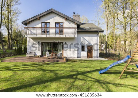 Big green backyard with slide for kids and a marble porch in the back of big modern house