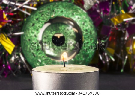 Big green carved mirror xmas ball with a candle on a background of tinsel - stock photo