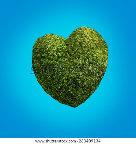 Big green heart made of plants on blue sky background - stock photo