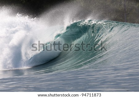 big green wave breaking in indonesia with trees at the background