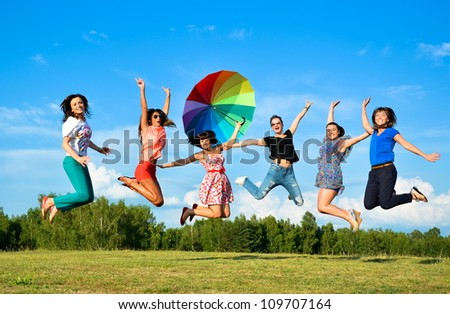 Big group of young girls with hands up jumping - stock photo