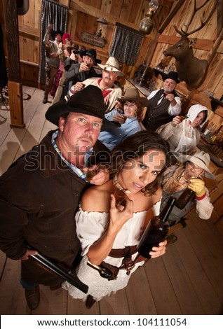 Big gunfighter and pretty woman in old western saloon - stock photo
