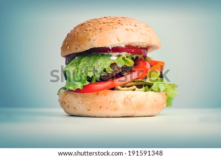 Big hamburger lays on the table above blue background, retro toned photo - stock photo