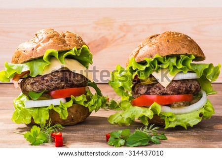 Big hamburger with beef cutlet and vegetables on wood plate