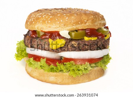 Big hamburger with jalapeno and vegetables on white background