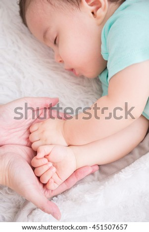 big hand hold cute baby fist and baby sleep on the white bed in bedroom, caucasian