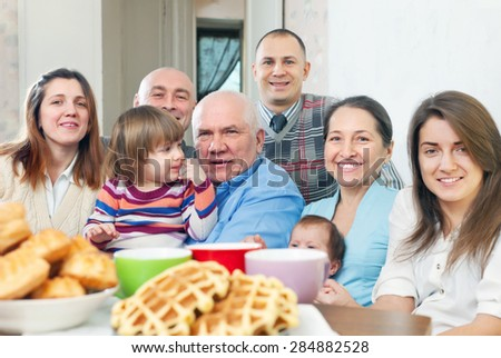 Big happy family having tea and baked at home
