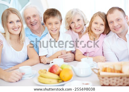 Big happy family looking at camera by dinner table - stock photo