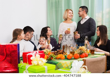 Big happy family sitting at holiday table, toasting and smiling