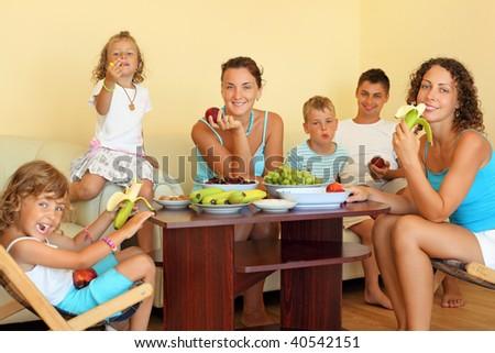 big happy family with children eats fruit in cozy room - stock photo