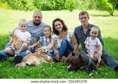 Big happy family with dogs and cat on the grass in the park - stock photo
