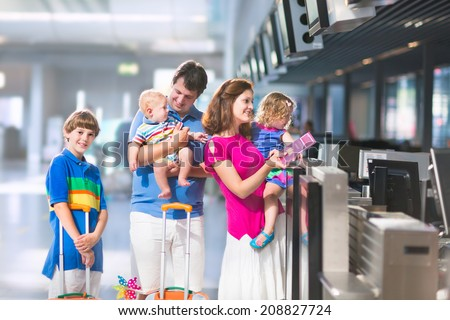 Big happy family with three kids traveling by airplane at Dusseldorf International airport, parents with teenager boy, toddler girl and little baby holding colorful luggage for summer beach vacation