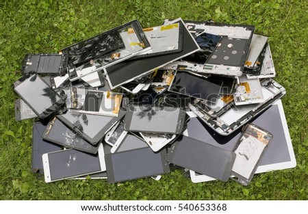 Big heap of the  broken mass production phones and  tablets lie on summer lawn. Modern technologies pollute environment concept outdoor shot