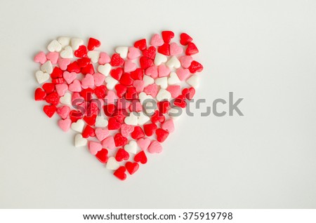 Big heart which consists of many little red, pink and white hearts on light background. Empty space for text. Valentines Day background. Valentine's Day theme. Romantic love background.  - stock photo