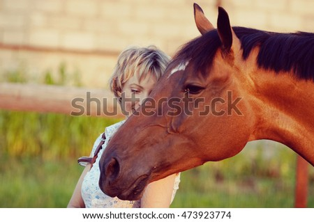 Big Horses head on womans shoulder. woman embrace brown horse