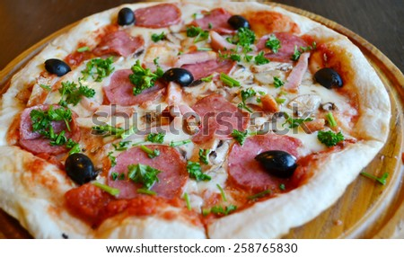 Big hot pizza with olives and salami